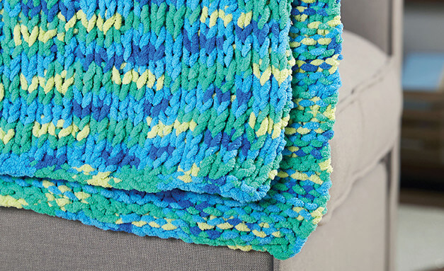 Image of blue knit blanket laying over a couch cushion.