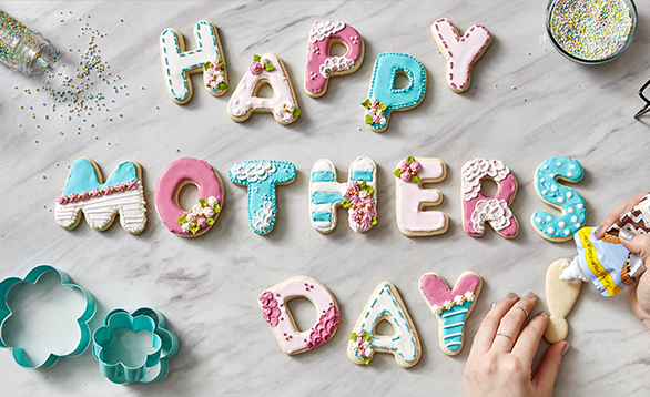 "image of cookies laying on table spelling out ""happy mothers day""."