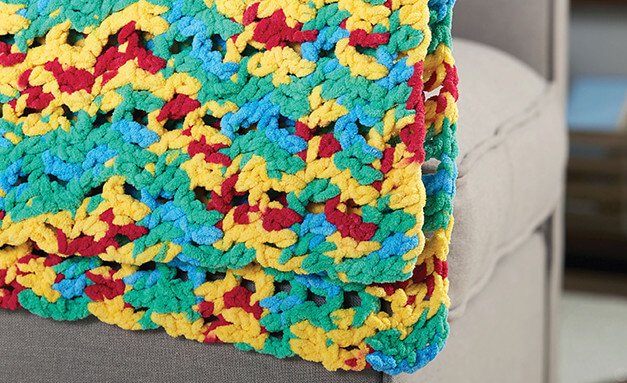 Image of multi-colored crocheted blanket laying over a couch cushion.