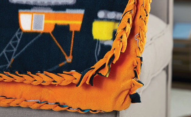 Image of orange and black no sew blanket laying over a couch cushion.
